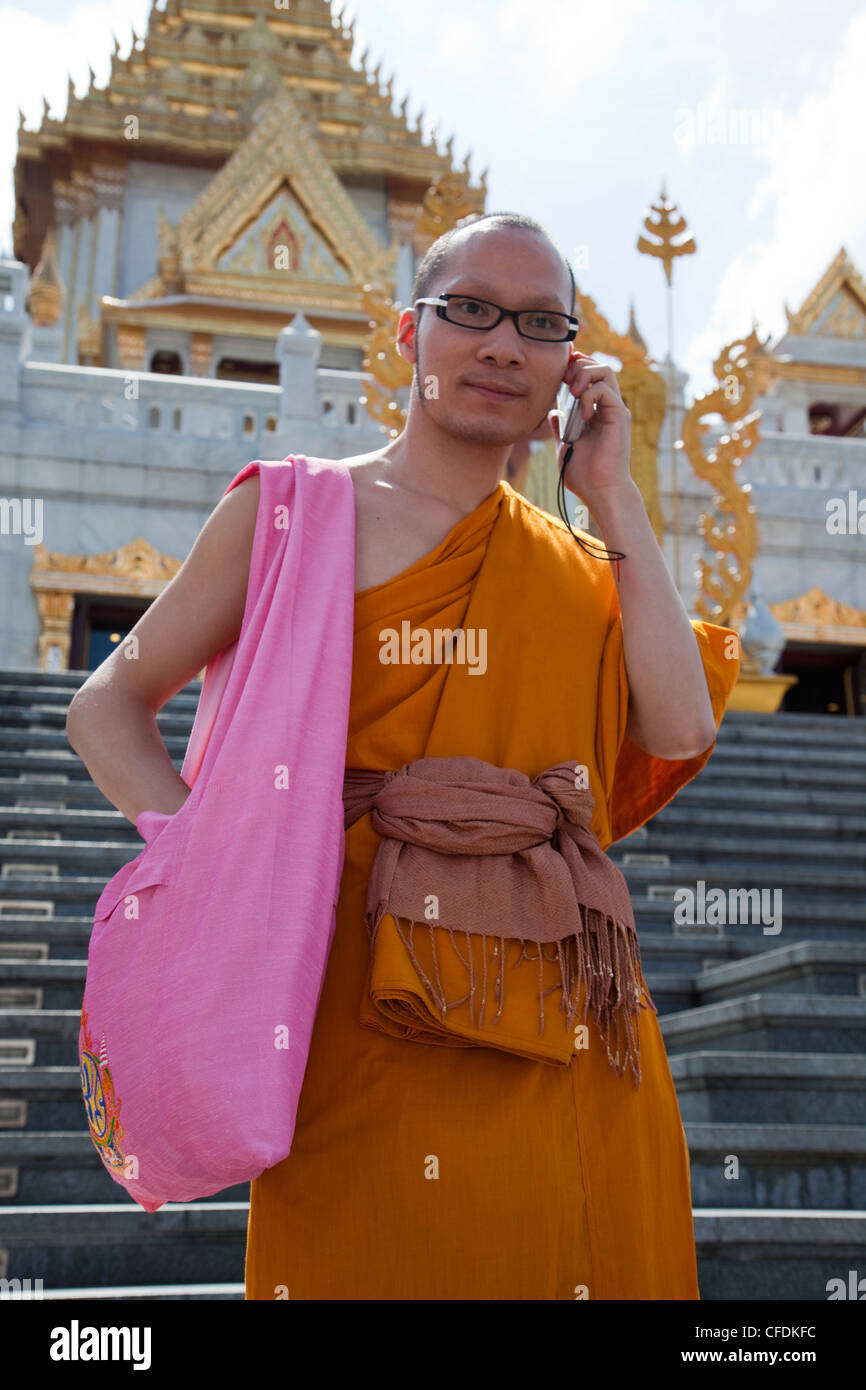 Monk with mobile phone in front of Wat Traimit, Temple of the Golden Buddha, Bangkok, Thailand - Stock Image