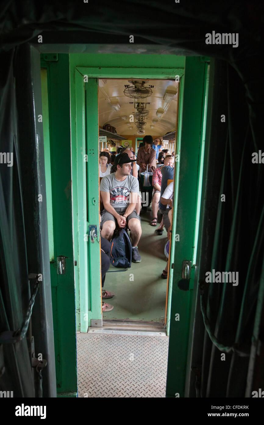 People in tourist train carriage on Trans River Kwai Death Railway, near Kanchanaburi, Thailand - Stock Image