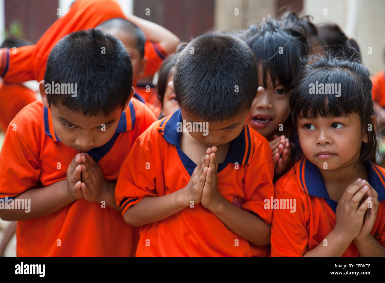 School children in uniform welcome visitors with wai greeting, near Kanchanaburi, Thailand Stock Photo