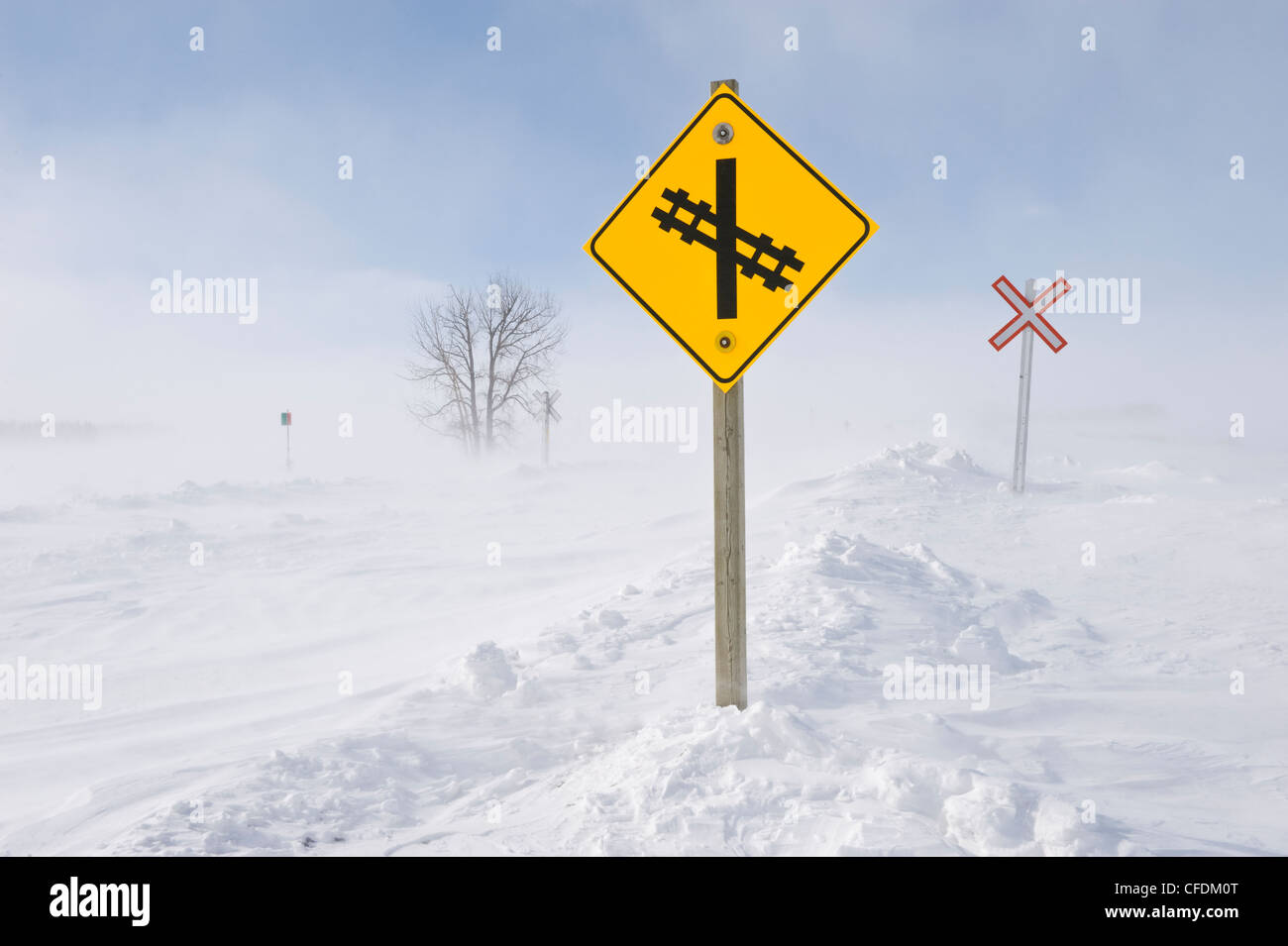 Road and railway covered with blowing snow, near Domain, Manitoba, Canada - Stock Image