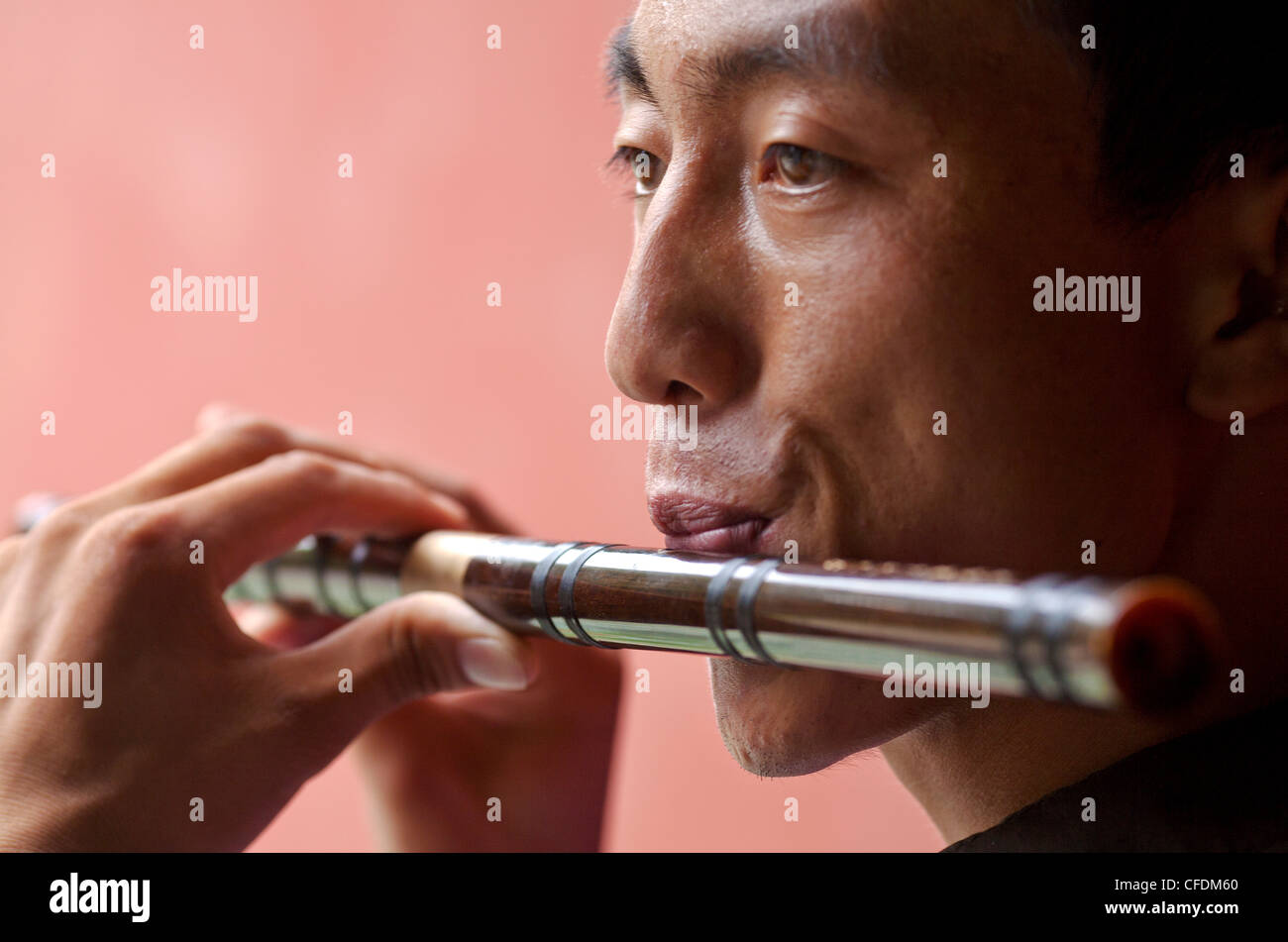 Closeup view of a young Chinese man playing a traditional Chinese flute, Beijing, China, Asia - Stock Image