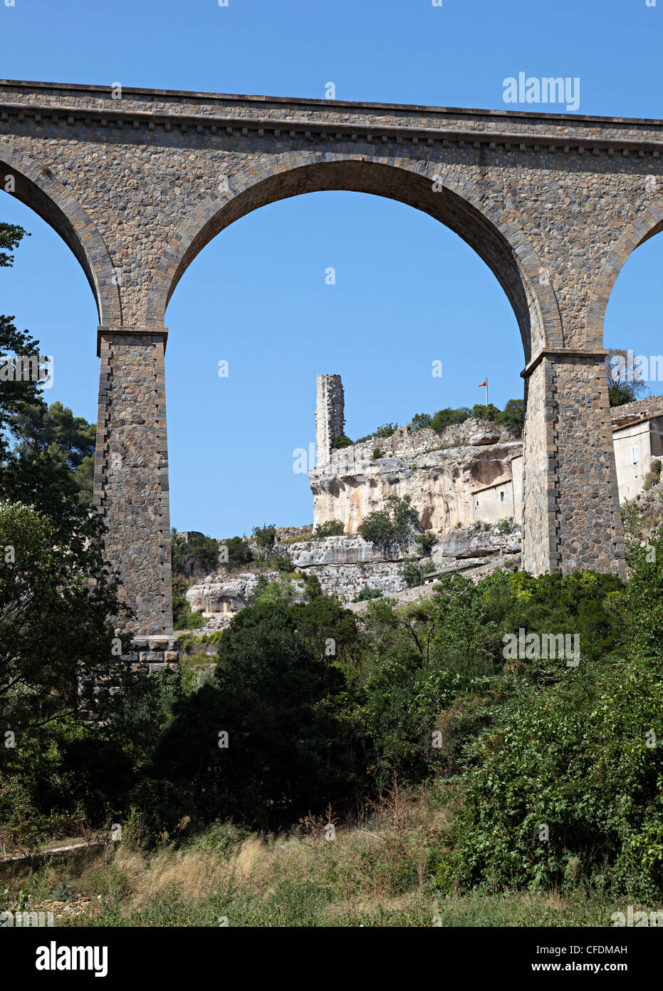 Ruined castle tower seen through arch of ancient bridge at Minerve, a Cathar Languedoc village, Herault, France - Stock Image