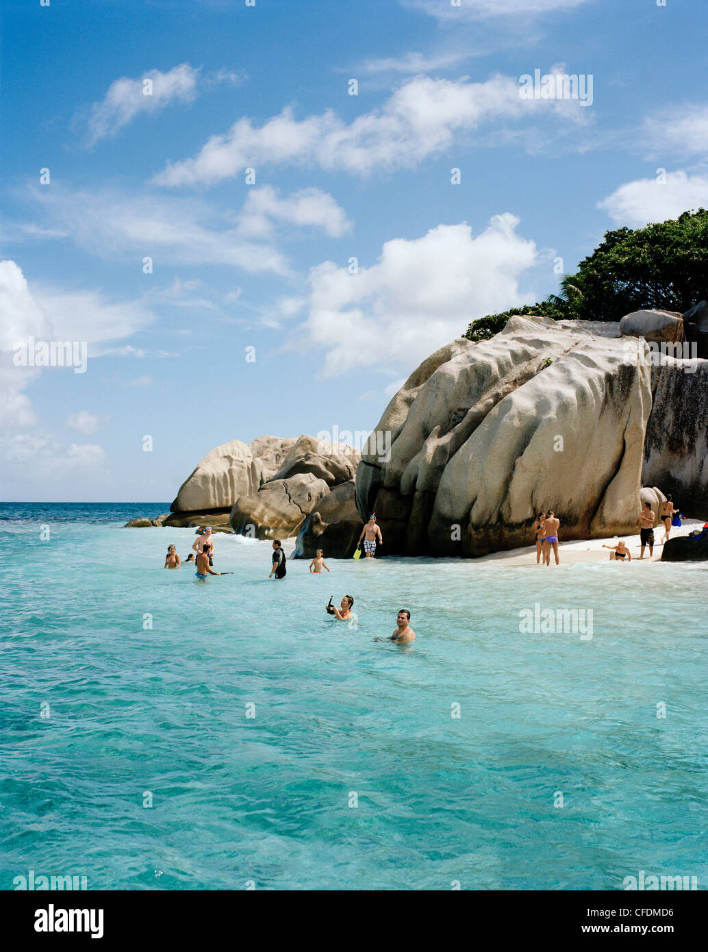 People snorkelling in shallow water over coral reef off tiny Coco Island, La Digue and Inner Islands, Republic of Stock Photo