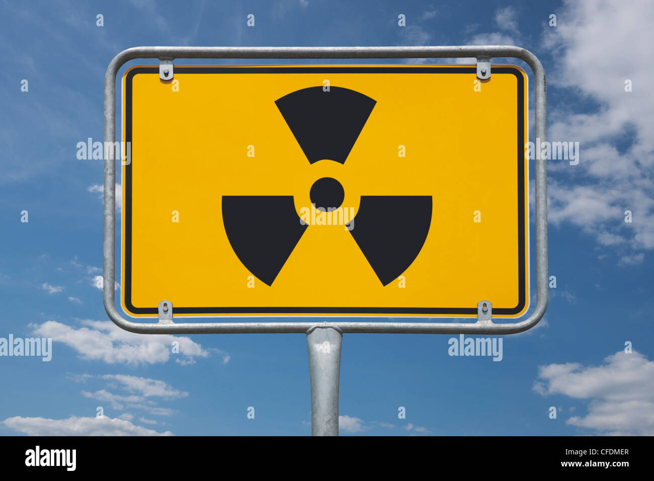 View of the entrance town sign with the symbol for radioactivity, background sky. - Stock Image