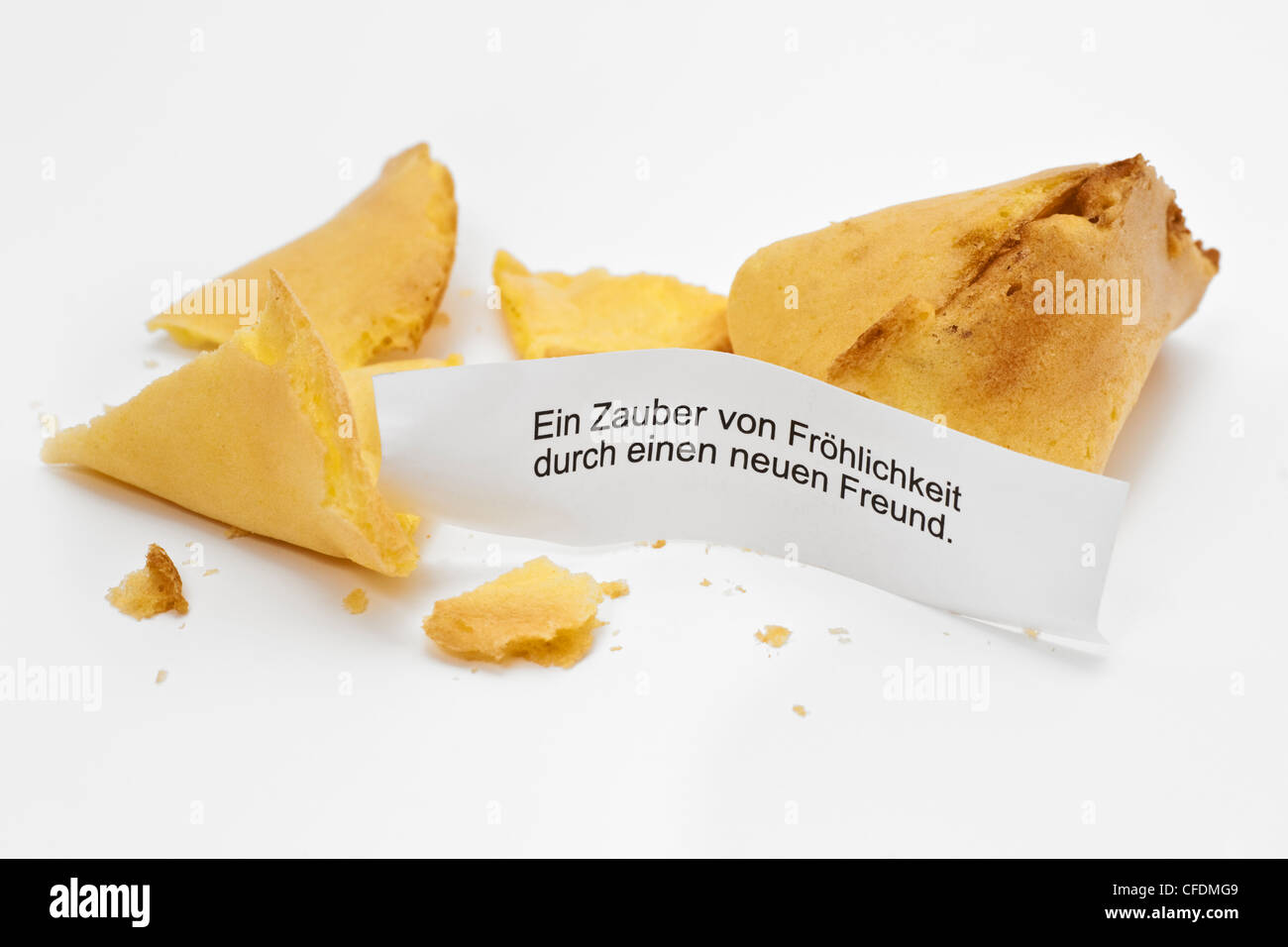 Detail photo of a fortune cookie, a slogan in German language is alongside. - Stock Image