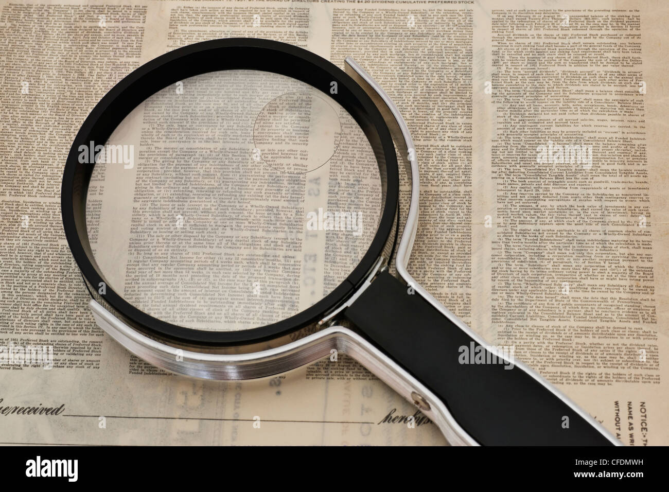 a magnifying glass is on a very small print terms and conditions - Stock Image