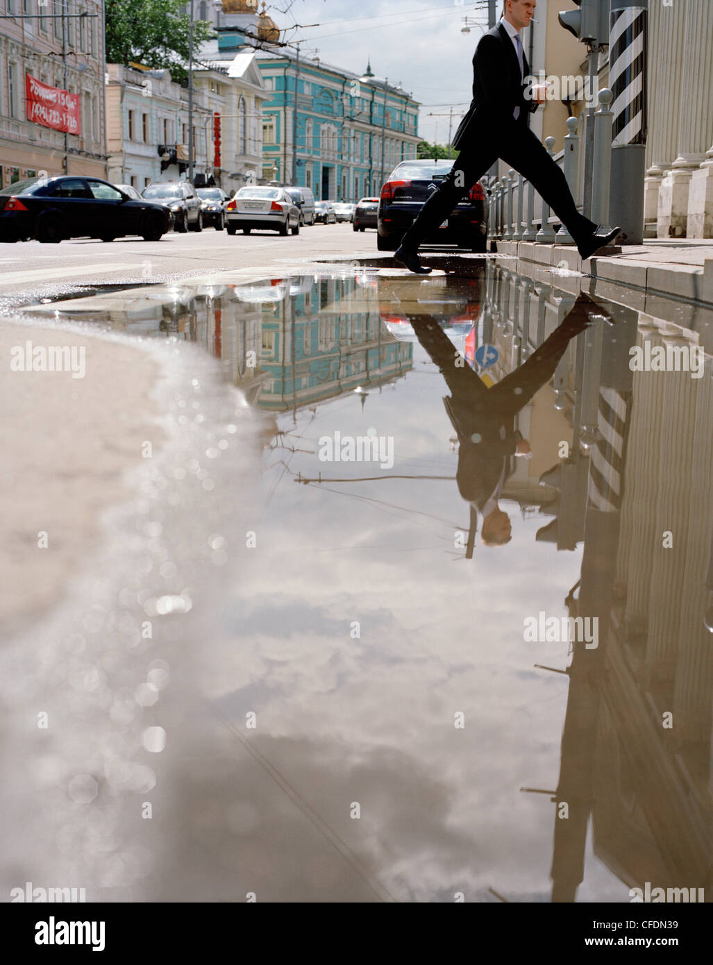 Pedestrian crossing a puddle in Wolchonka Uliza street, Moscow, Russia, Europe - Stock Image