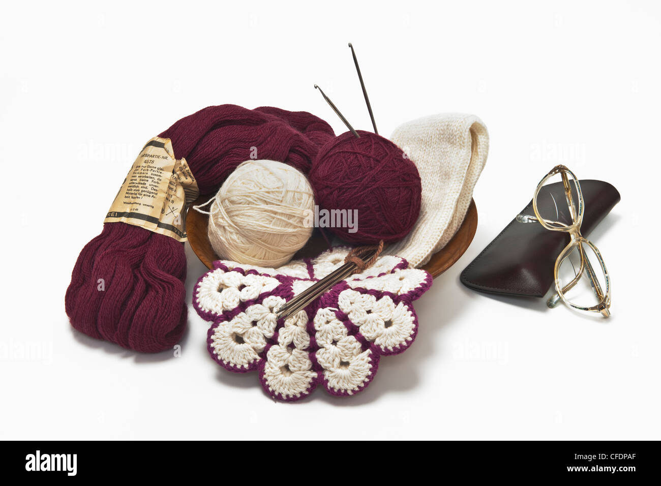 different wool, a potholder, knitting needles and glasses are close to each other - Stock Image