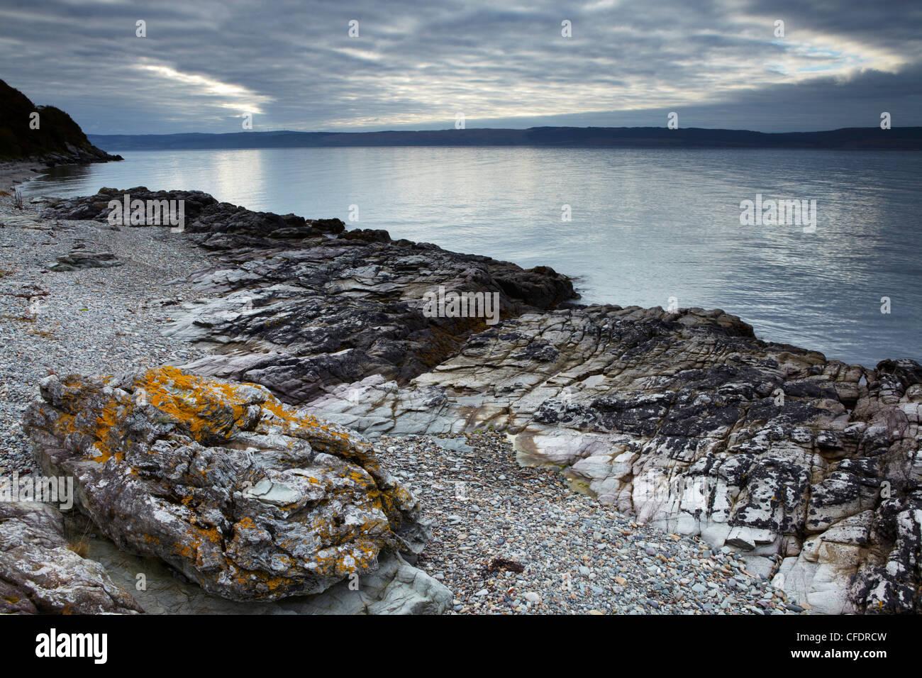 The coast of the Isle of Arran near Catacol looking across towards the Kintyre Peninsula on the Scottish mainland, - Stock Image