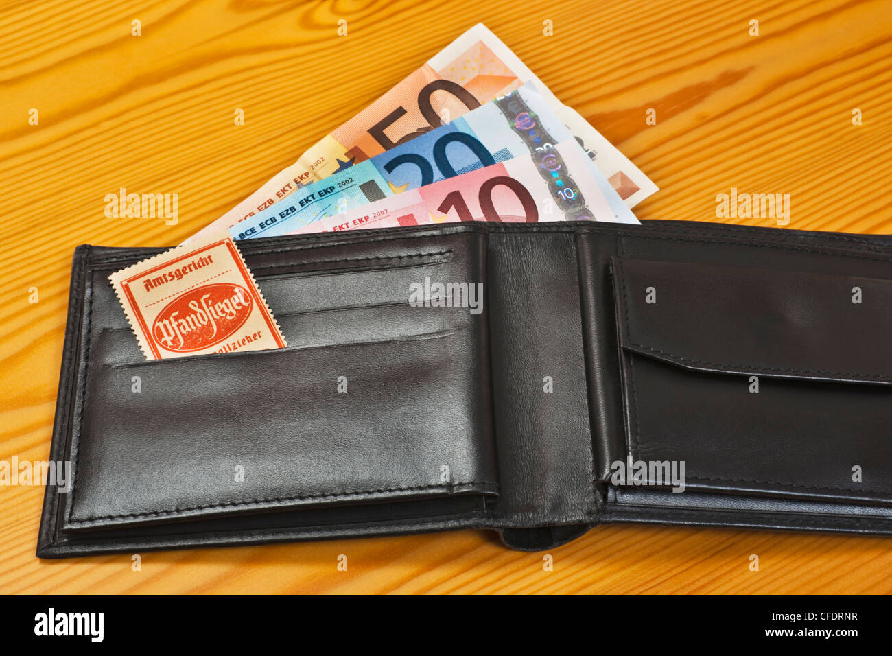 An open purse with Euro Banknotes, inside is a bailiff's seal for distraint of goods. Stock Photo