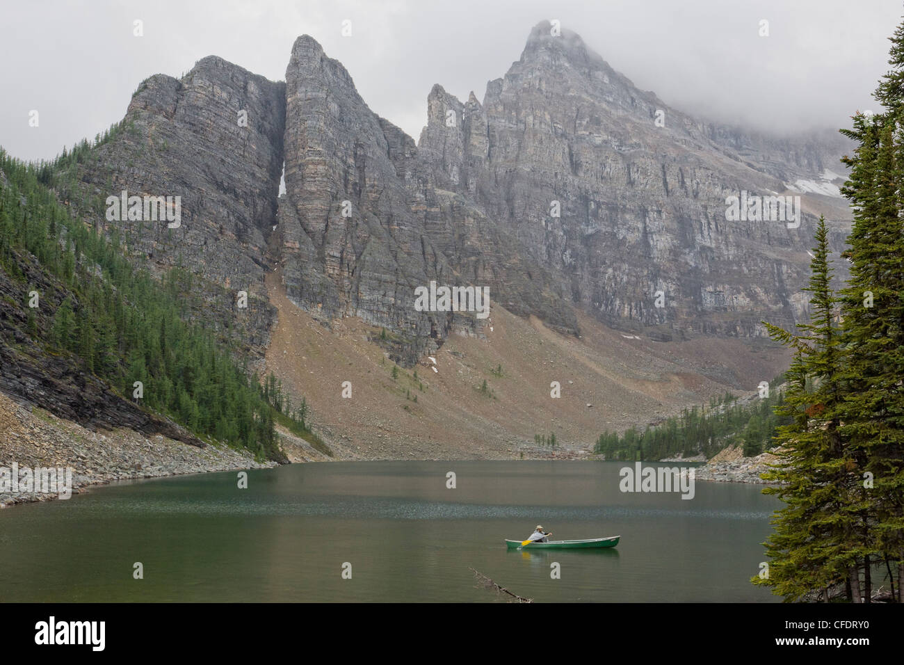 Man canoeing on Lake Agnes on a rainy day in Banff National Park, Alberta, Canada - Stock Image