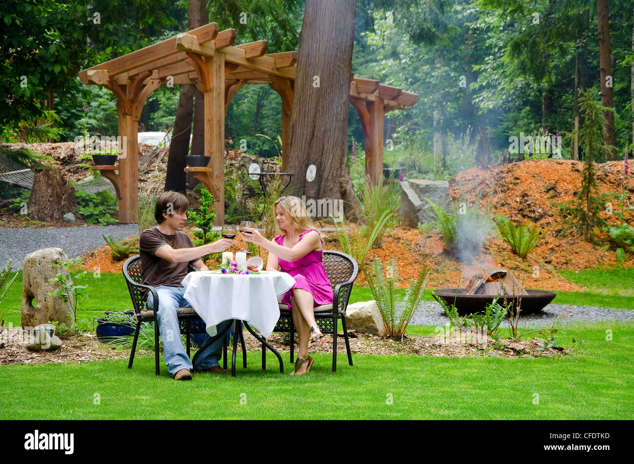 Young couple enjoy fireside dinner Savary Island - Stock Image