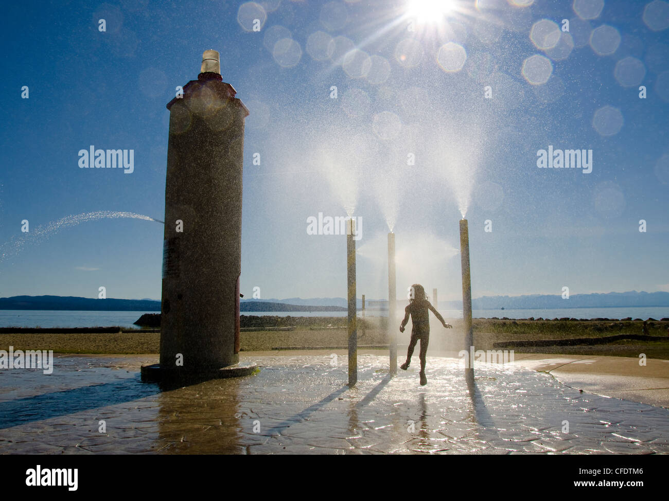 Young child plays water park Willingdon Beach - Stock Image