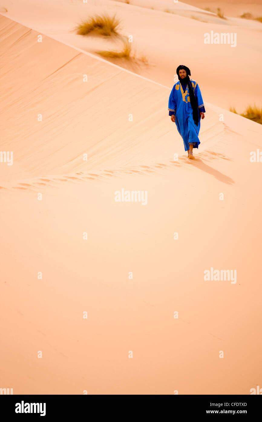 Berber man in blue robe walking along the ridge of a sand dune in the Erg Chebbi sand sea near Merzouga, Morocco, - Stock Image