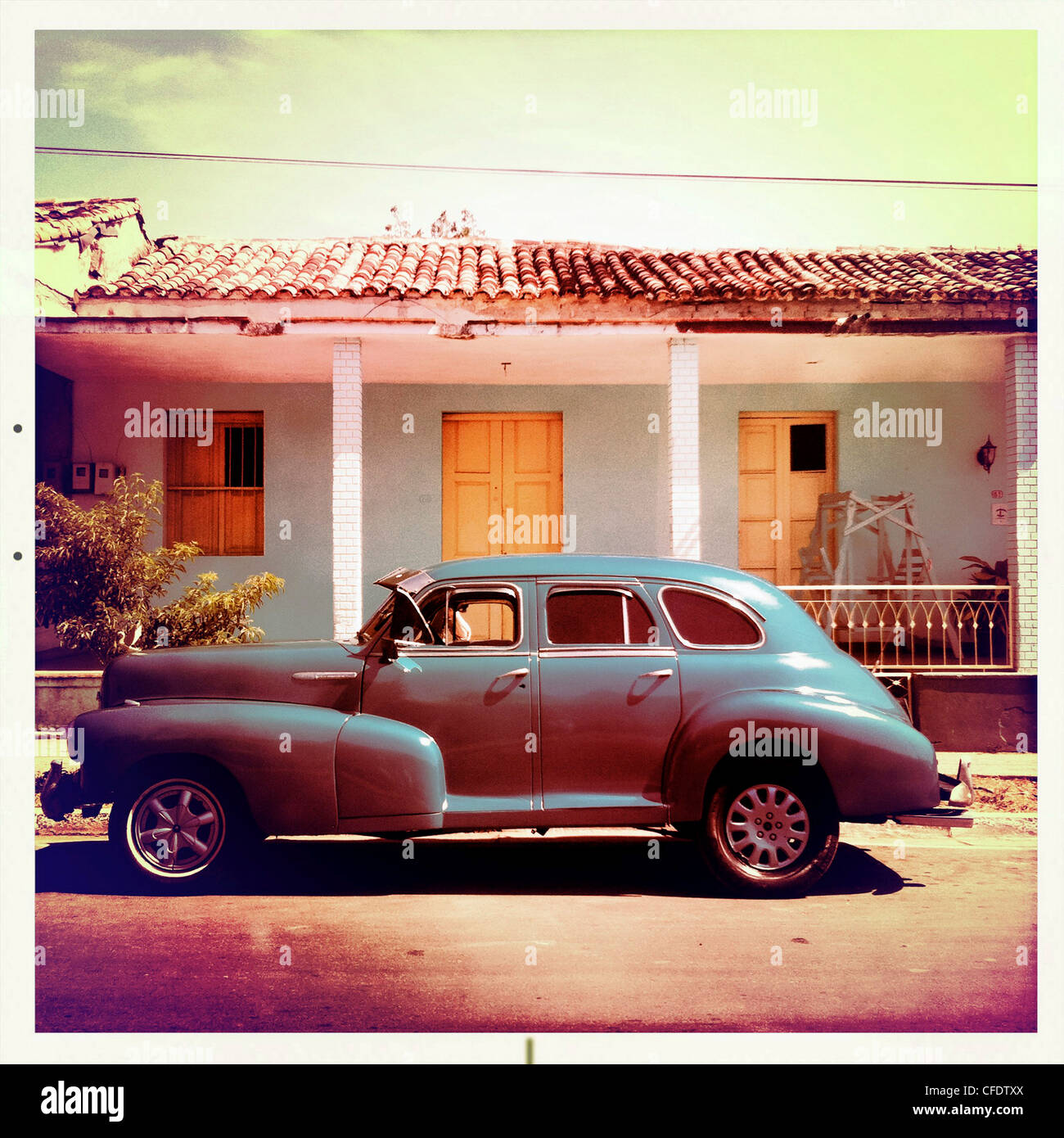 Classic American car parked on a street with traditional,in the background, Trinidad, Cuba, West Indies, Central - Stock Image
