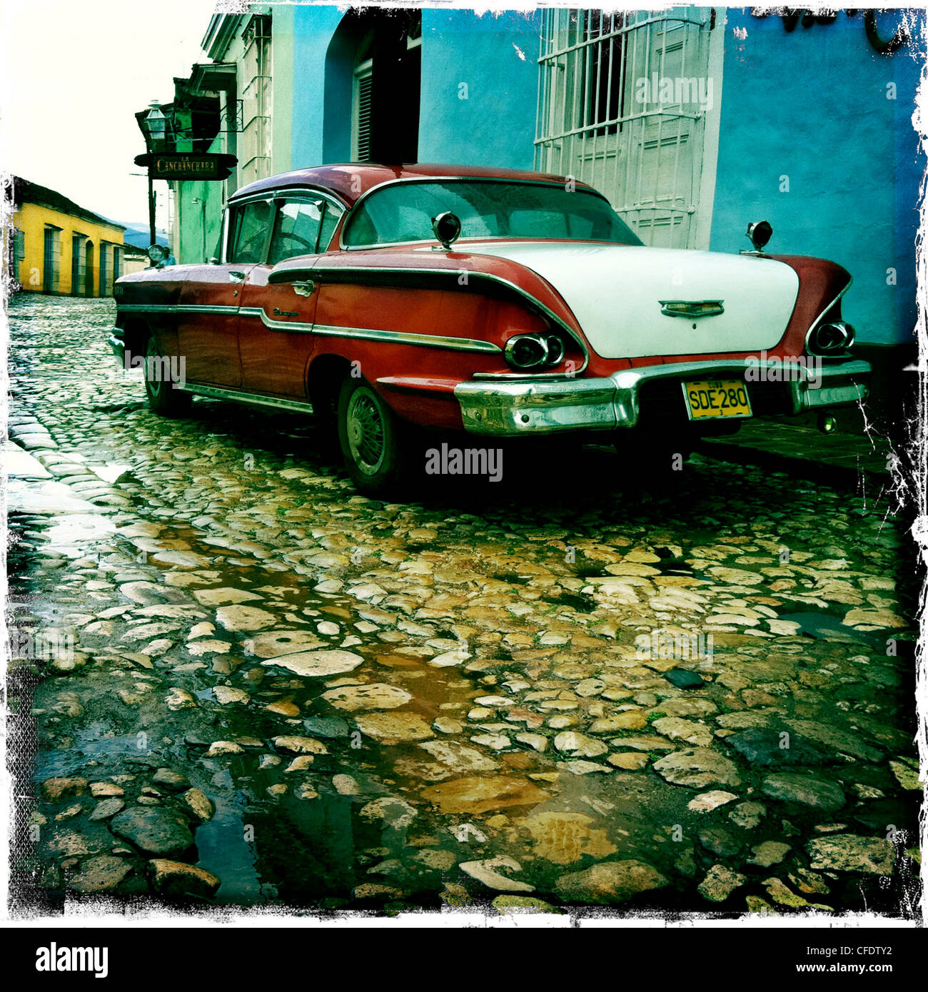 Old American car parked on a cobbled street in the town of Trinidad, Cuba, West Indies, Central America - Stock Image