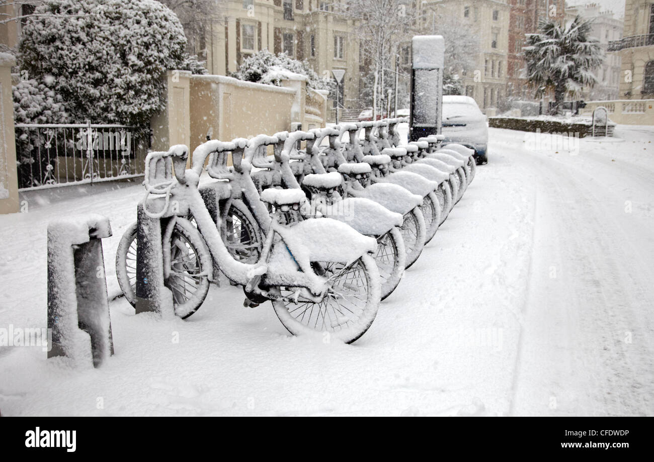 Rows of hire bikes in snow, Notting Hill, London, England, United Kingdom, Europe - Stock Image