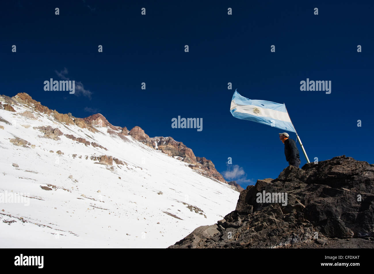 Hiker under the Argentinian flag looking up at the summit of Aconcagua, Aconcagua Provincial Park, Andes mountains, - Stock Image
