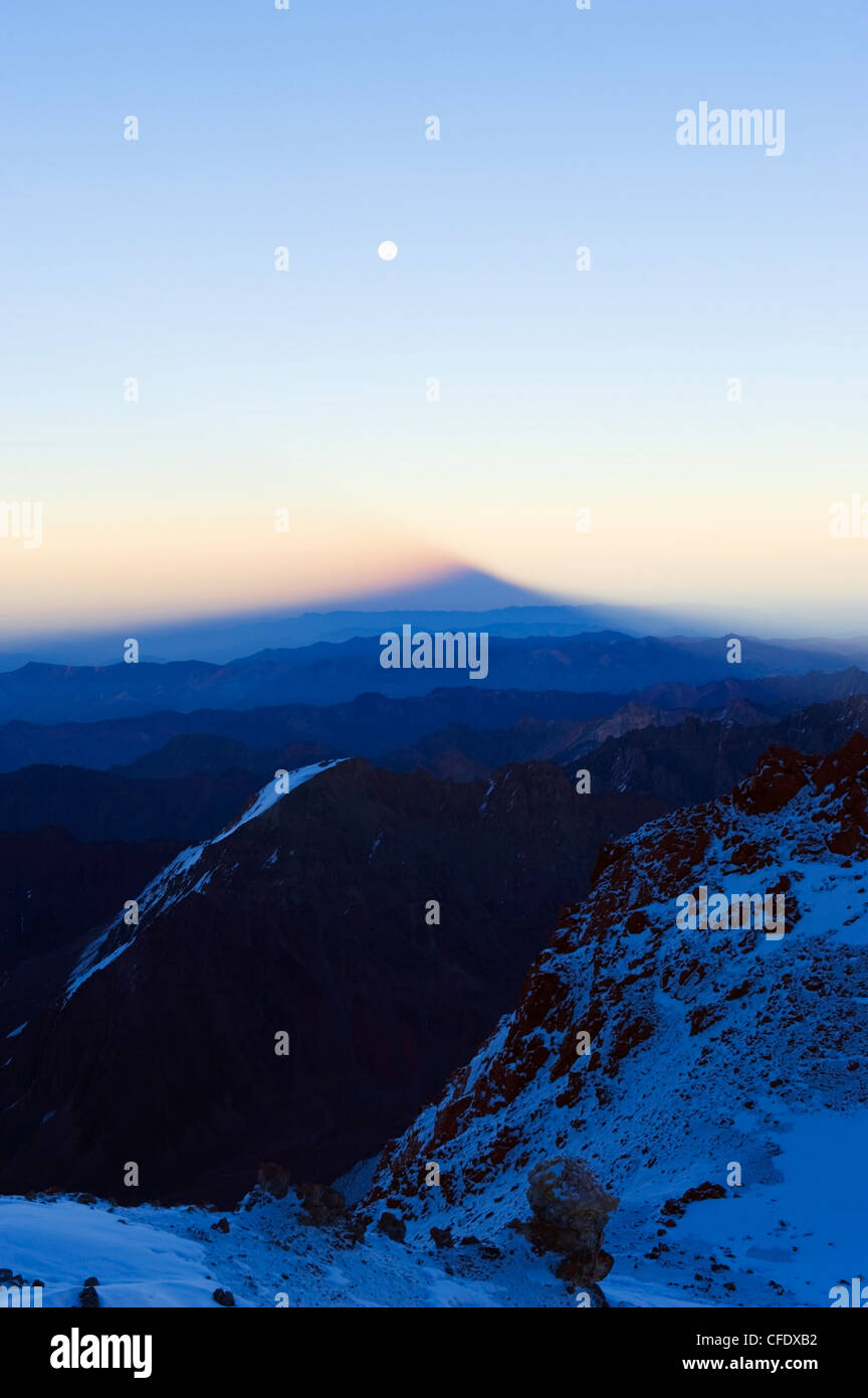 Full moon at sunrise and shadow of Aconcagua, Aconcagua Provincial Park, Andes mountains, Argentina - Stock Image
