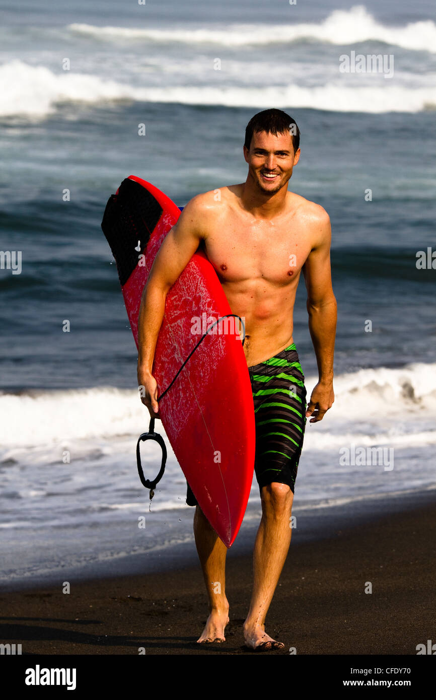 A male surfer wearing board shorts walks up the beach at Pasquales, Mexico while holding a red surfboard under his Stock Photo