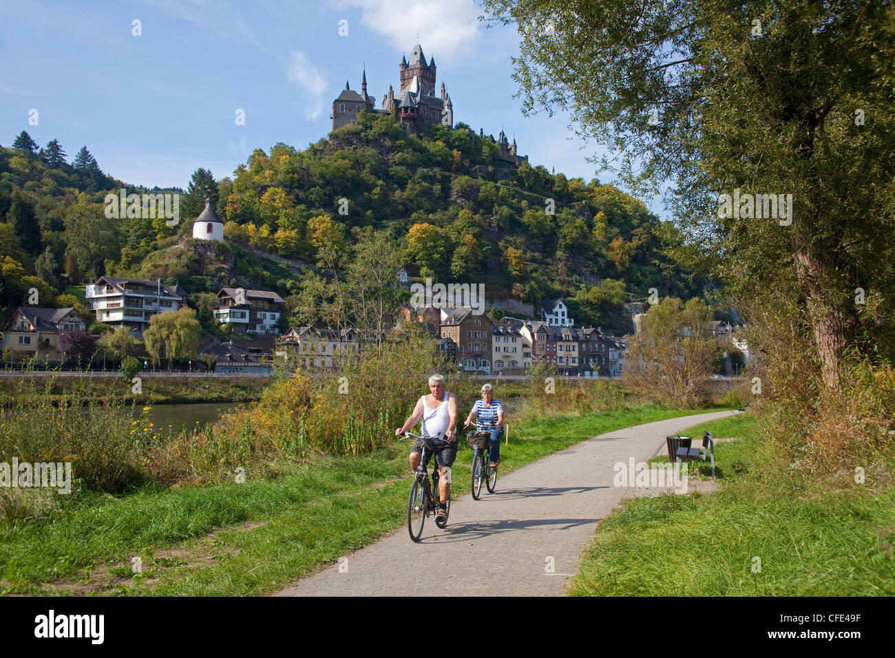 Cyclists on a cycleway at riverside of Moselle river, Cochem with castle, Rhineland-Palatinate, Germany, Europe - Stock Image