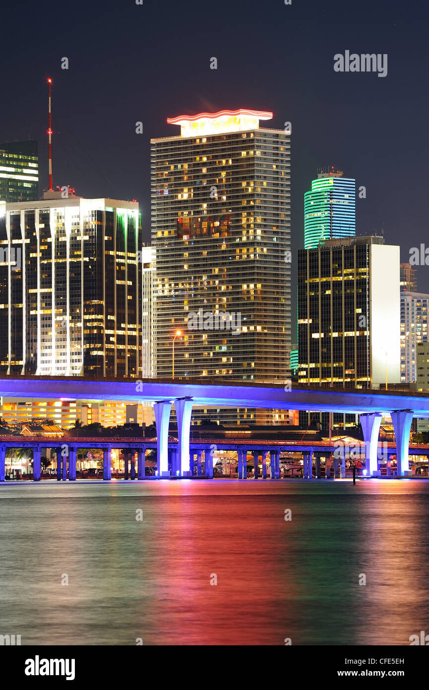 Miami city skyline closeup at dusk with urban skyscrapers and bridge over sea with reflection - Stock Image
