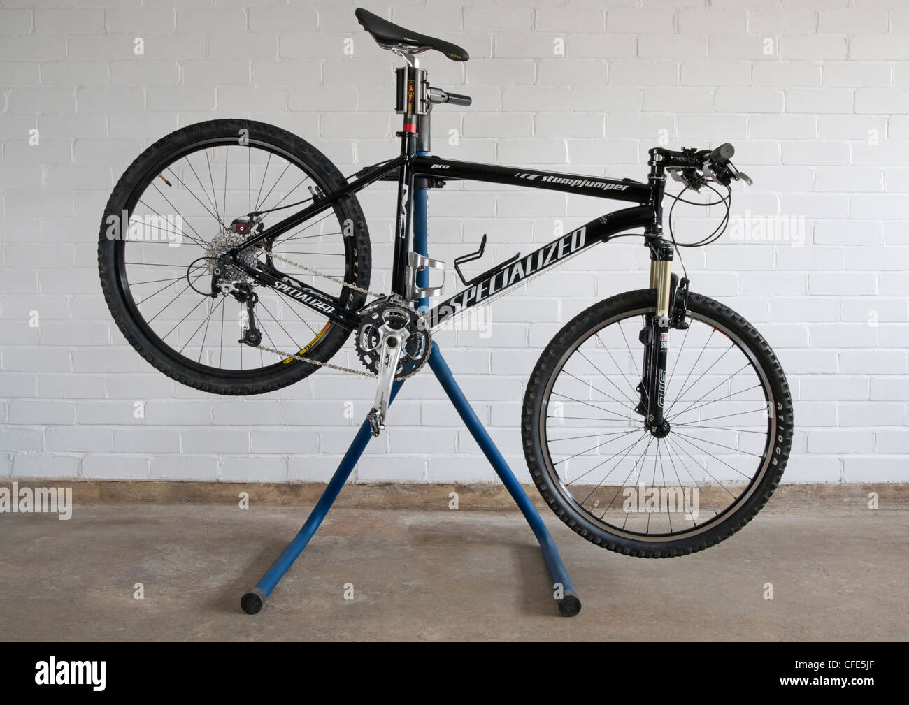 Mountain bike on bicycle work stand against brick wall - Stock Image
