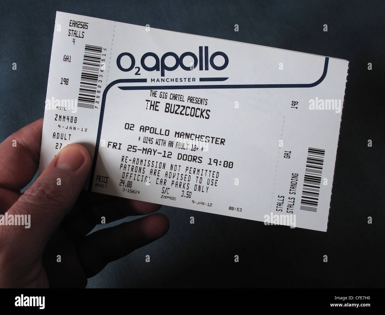 Buzzcocks concert ticket for Manchester Apollo 25th May 2012 with Howard Devoto held in an hand - Stock Image