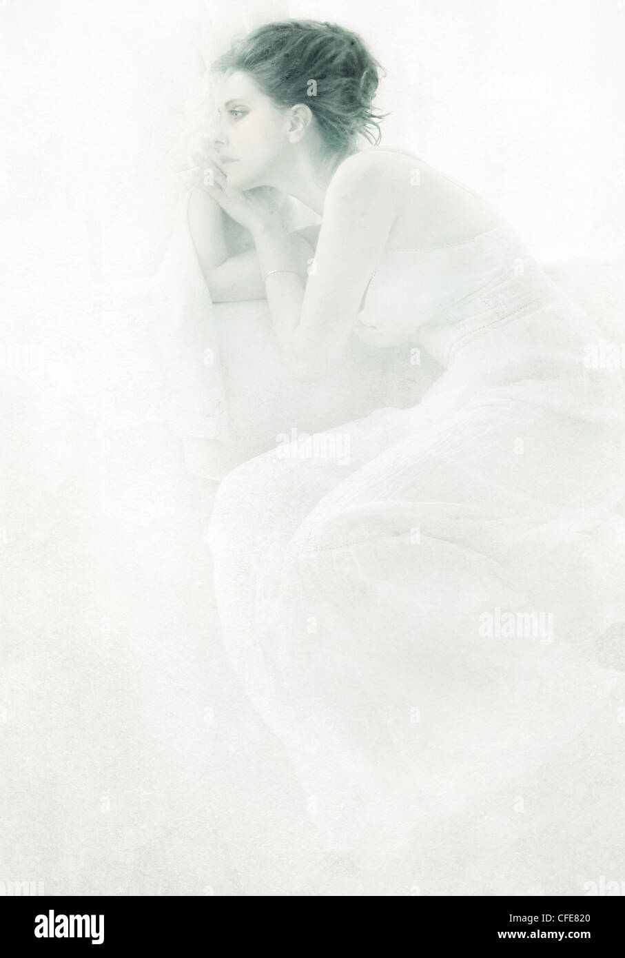A young woman relaxing wearing a white dress looking into distance - Stock Image