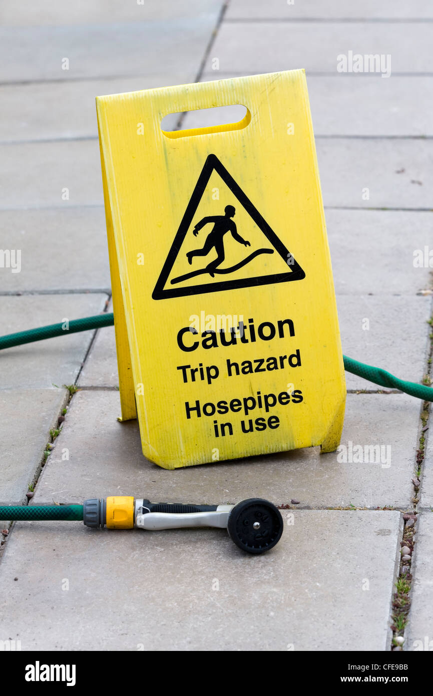 trip hazard sign warning of hosepipes in use - Stock Image