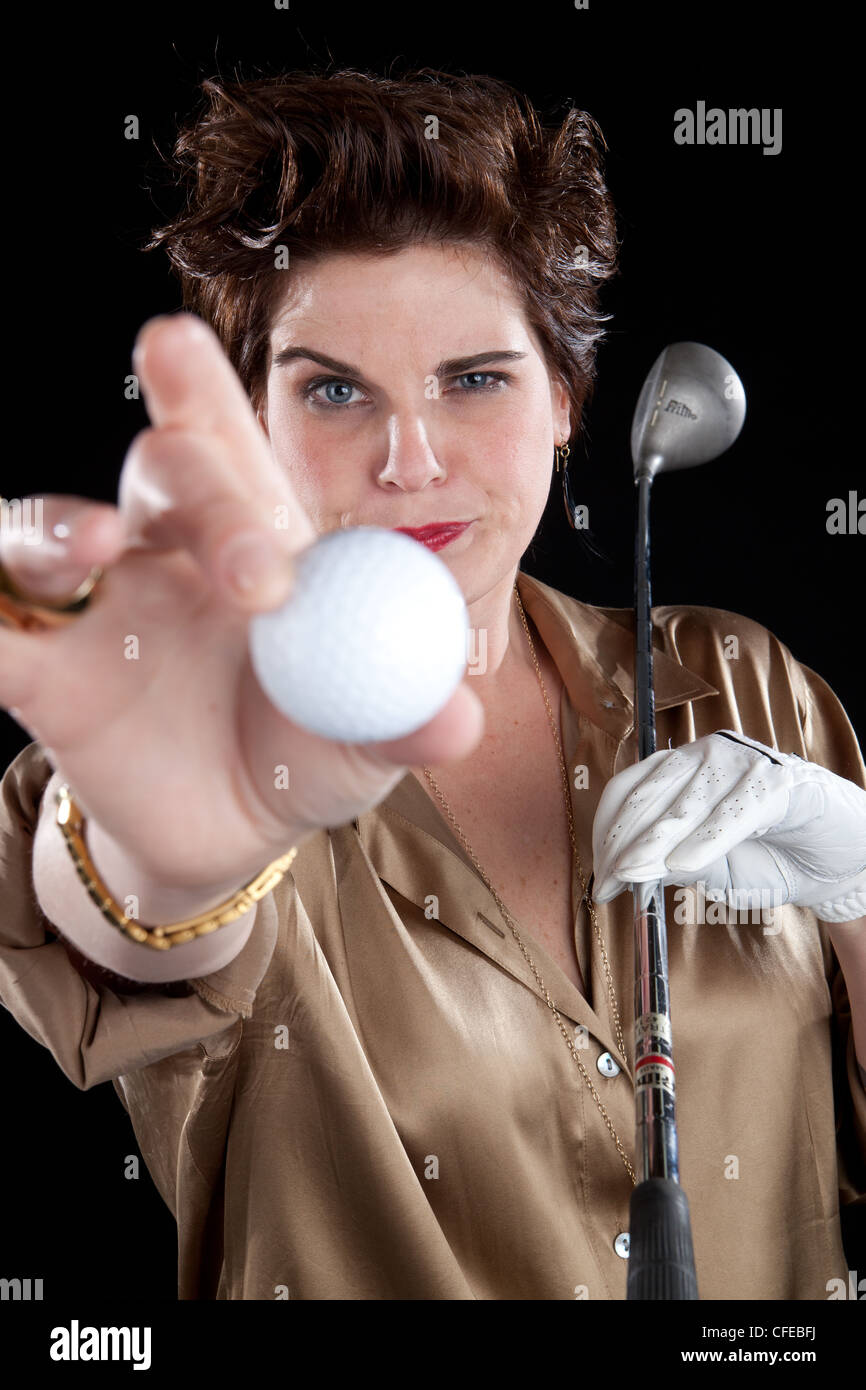 Elegant woman holds golf club and extends golf ball toward camera with a funny expression on her face. - Stock Image