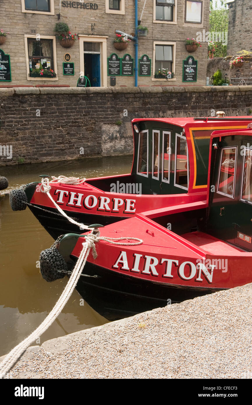 Front of 2 bright red canal boats (names on bow) moored side by side by towpath & canalised pub - Leeds-Liverpool Stock Photo