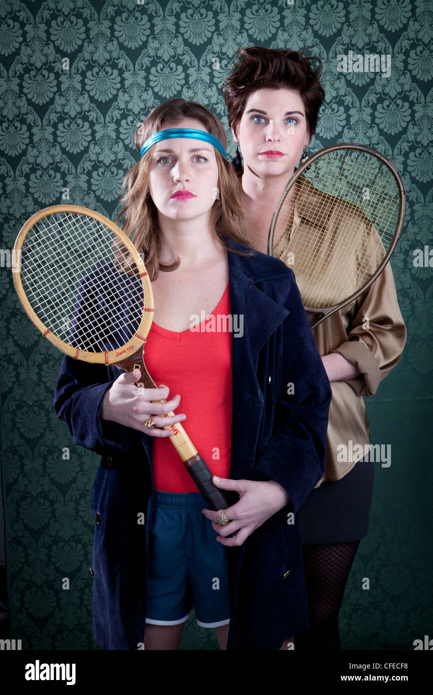 Two Women With Tennis Rackets In Front Of Vintage Wallpaper