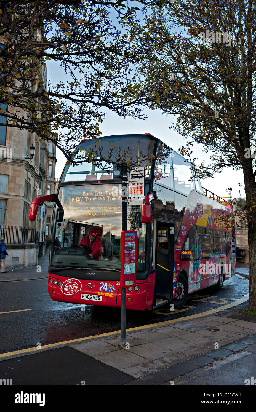 A double decker bus waits in evening sunshine at a bus stop in Bath, UK Stock Photo