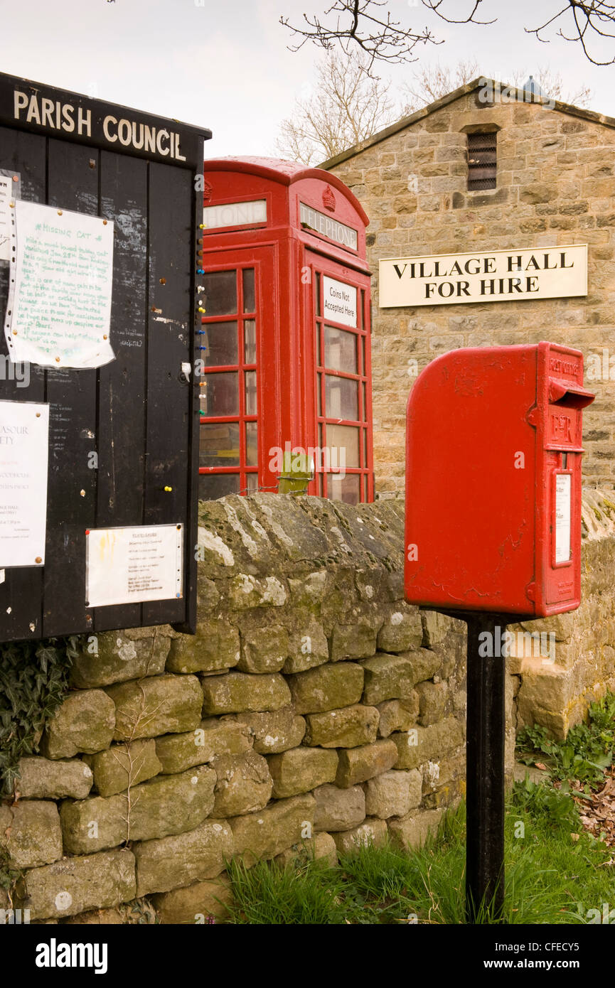 Street furniture - parish noticeboard, red post box & iconic K6 telephone box by village hall (for hire sign) - Stock Photo