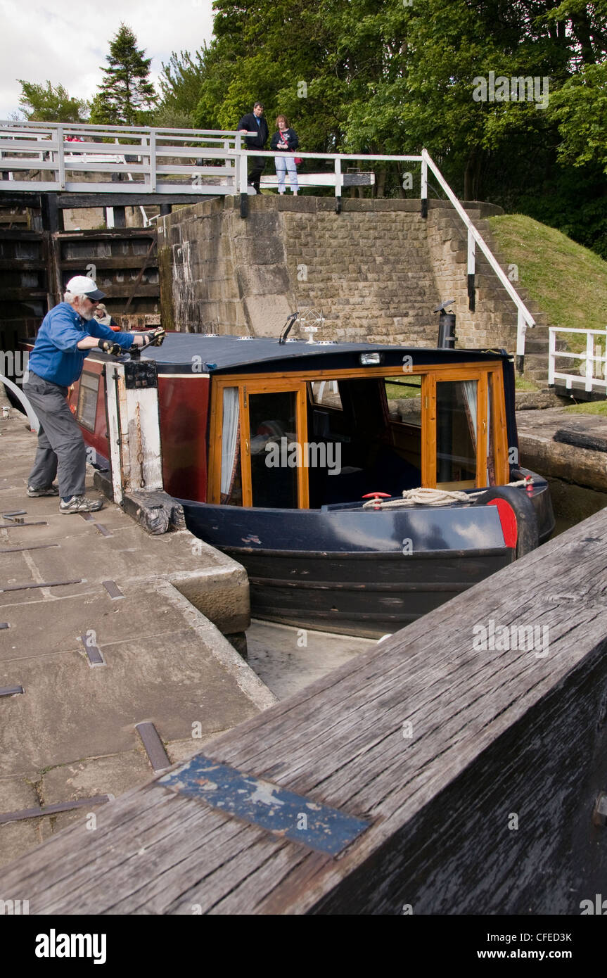 Narrowboat in lock chamber passing through The Five Rise Locks on Leeds Liverpool Canal (man winding handles to Stock Photo