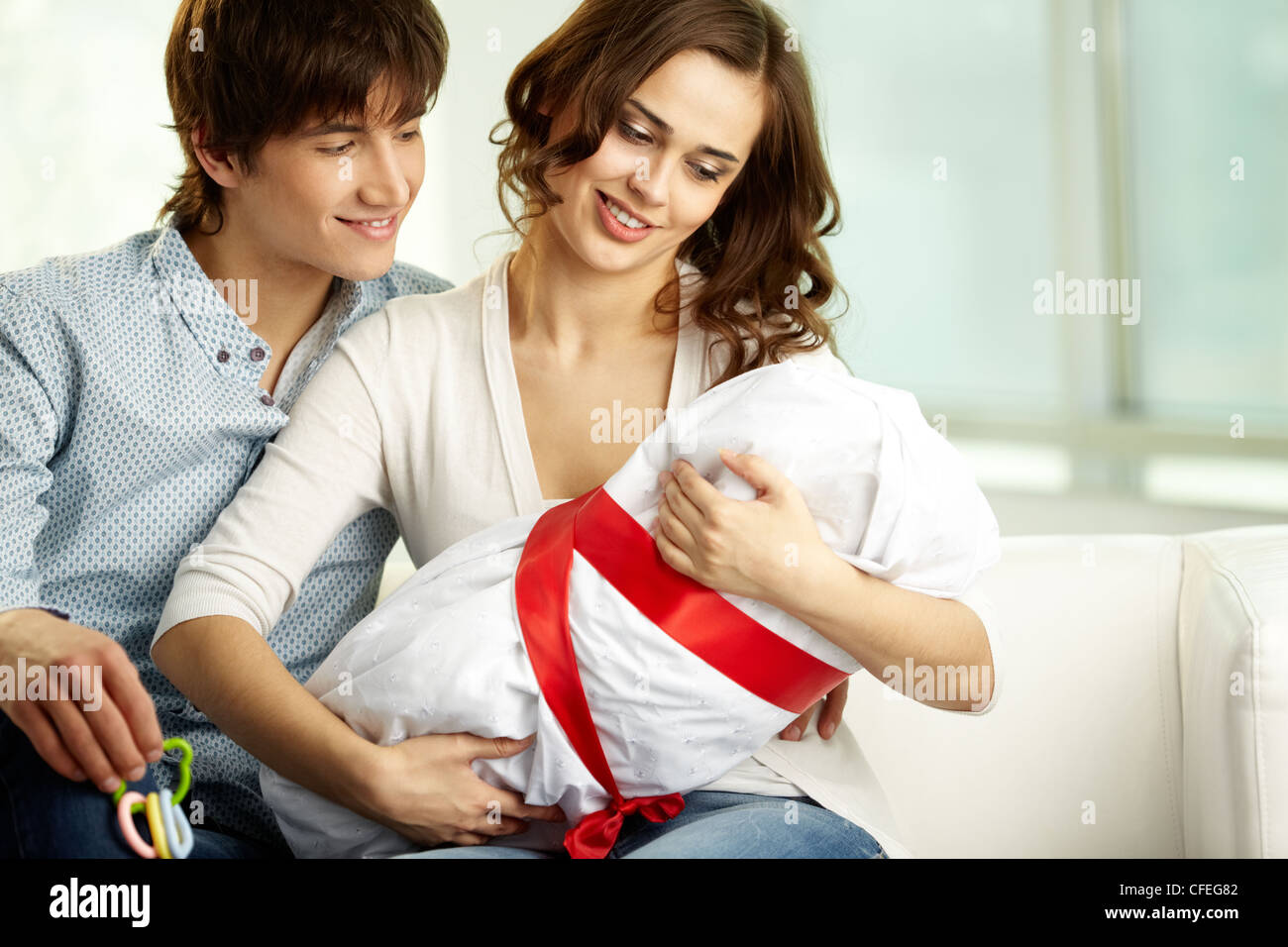 Young woman holding her newborn baby in, her husband smiling happily - Stock Image