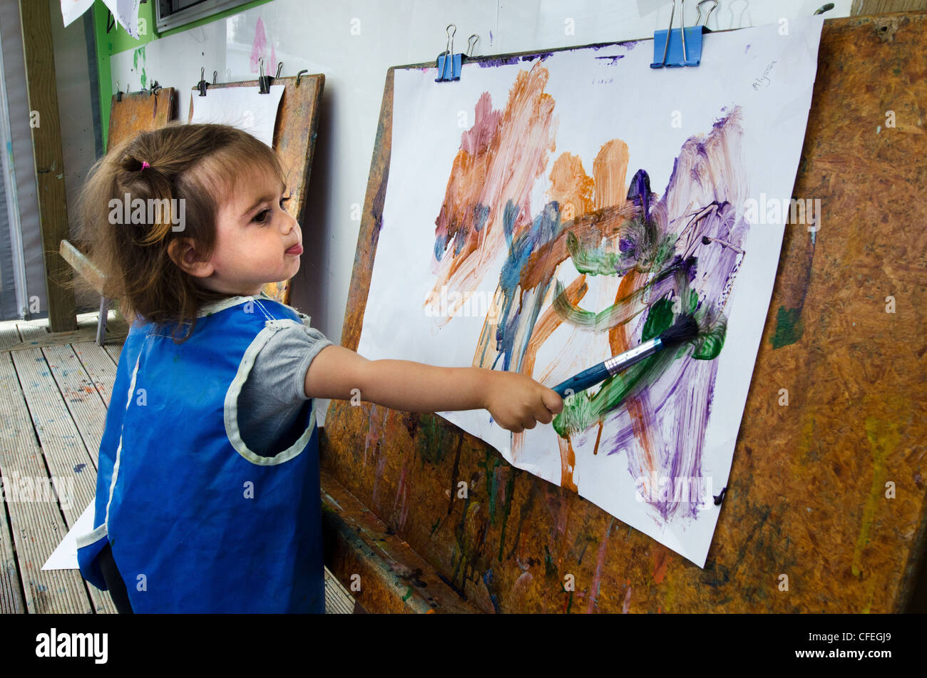 Adorable little girl sticks her tounge out while concentrating on painting a picture at a preschool centre - Stock Image