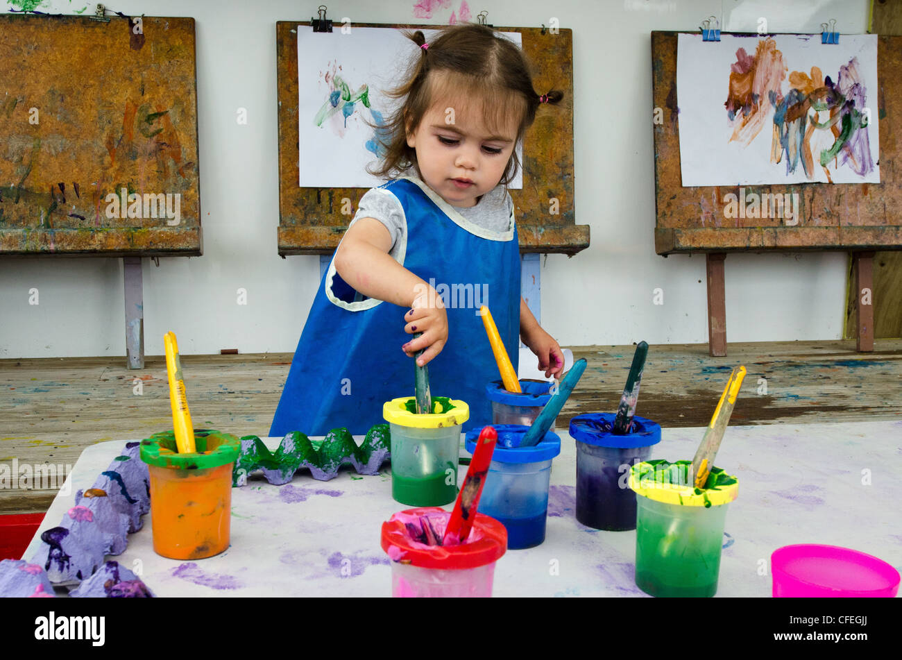 Little girl paints at a playground - Stock Image