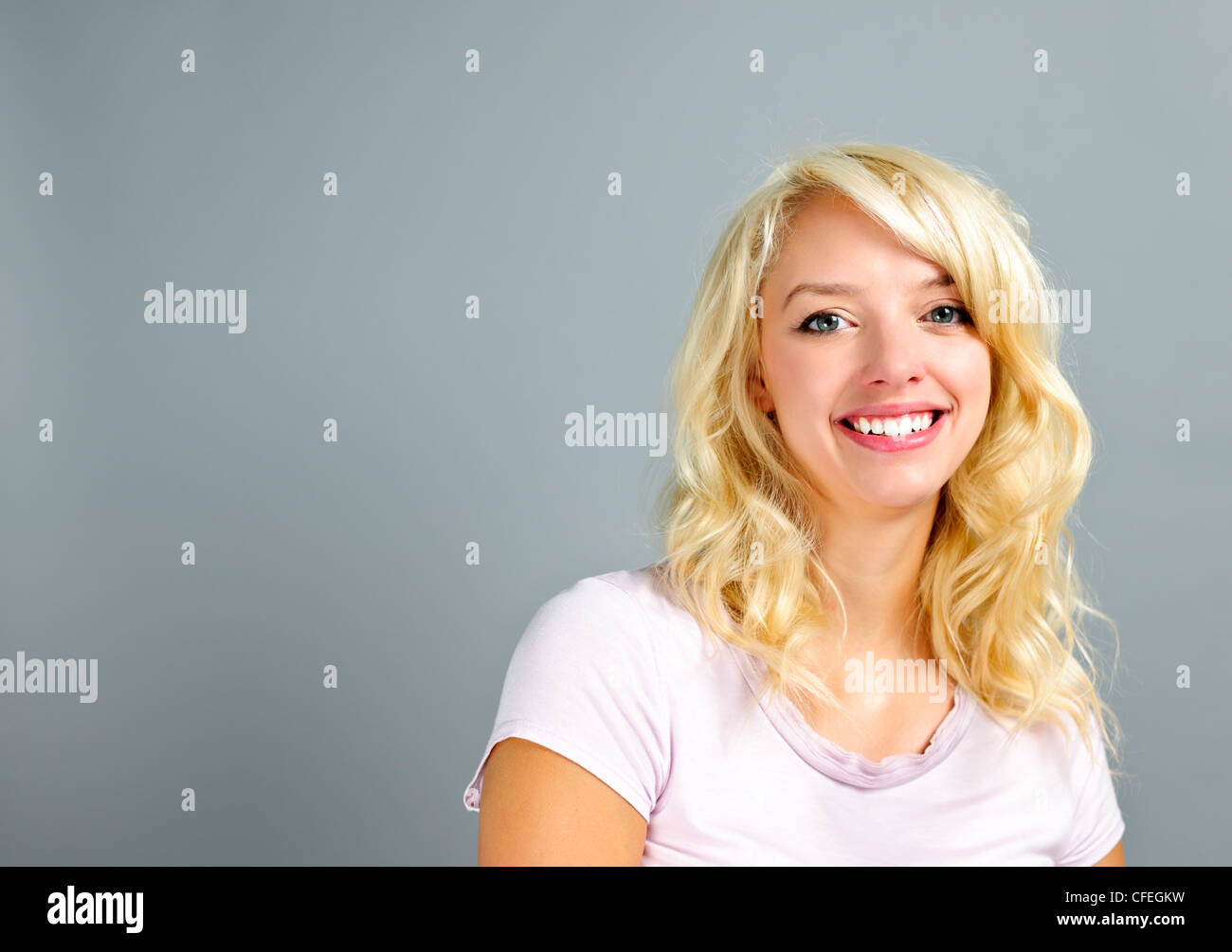 Portrait of smiling young blonde caucasian woman on grey background - Stock Image