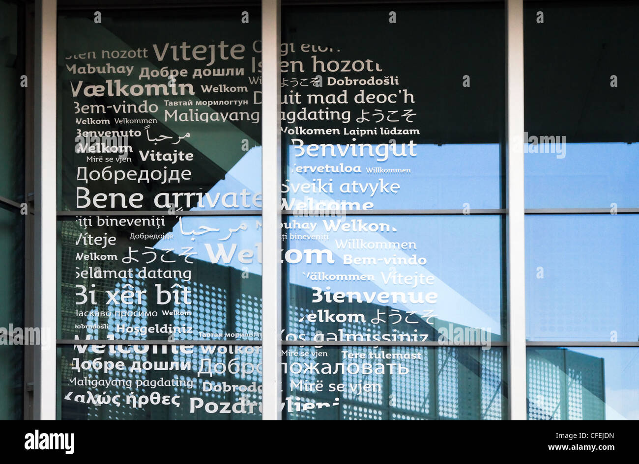 Welcome in many languages in shape of letter B on glass windows. - Stock Image