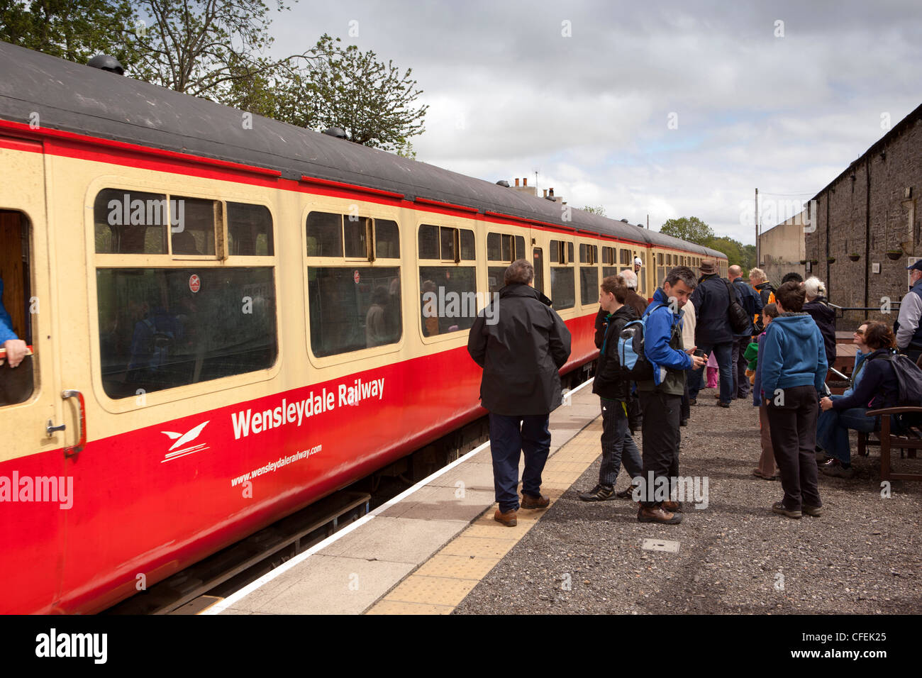 UK, England, Yorkshire, Leyburn station, passengers boarding Wensleydale Railway train at platform - Stock Image