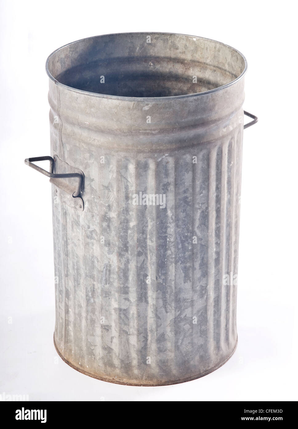 An old corrugated metal garbage bin with folding handles and lid. studio shot on white background. - Stock Image