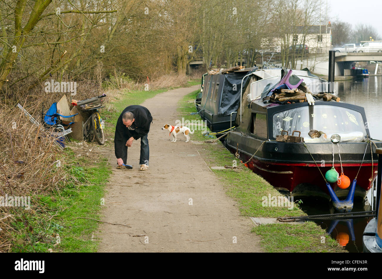 Man sweeping and brushing canal towpath with brush by moored narrow boats Grand Union canal Rickmansworth Herts - Stock Image