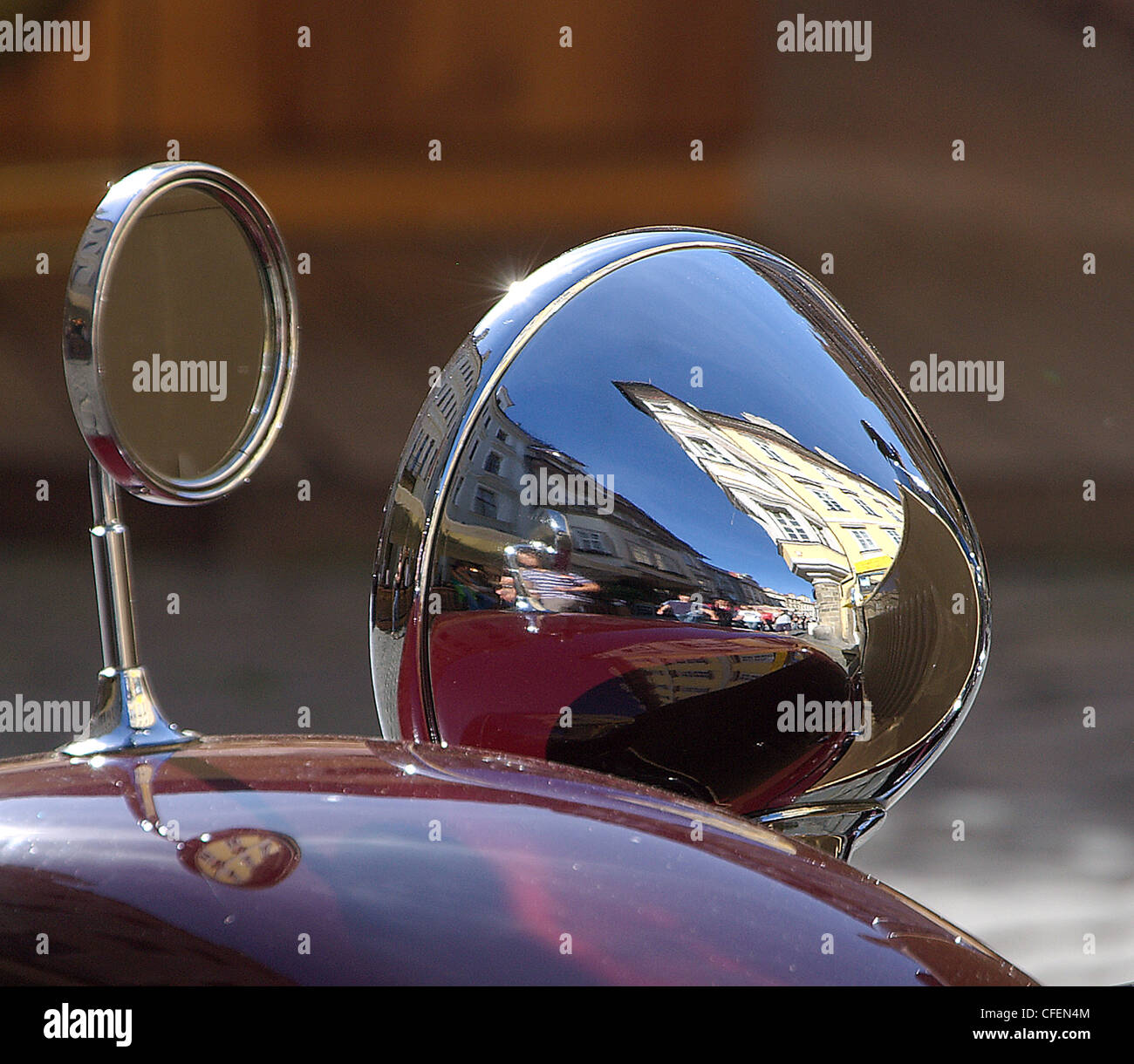 Distorted reflection of a an old town square in Summer in the chromed headlight of a vintage car. Double reflection of the image Stock Photo