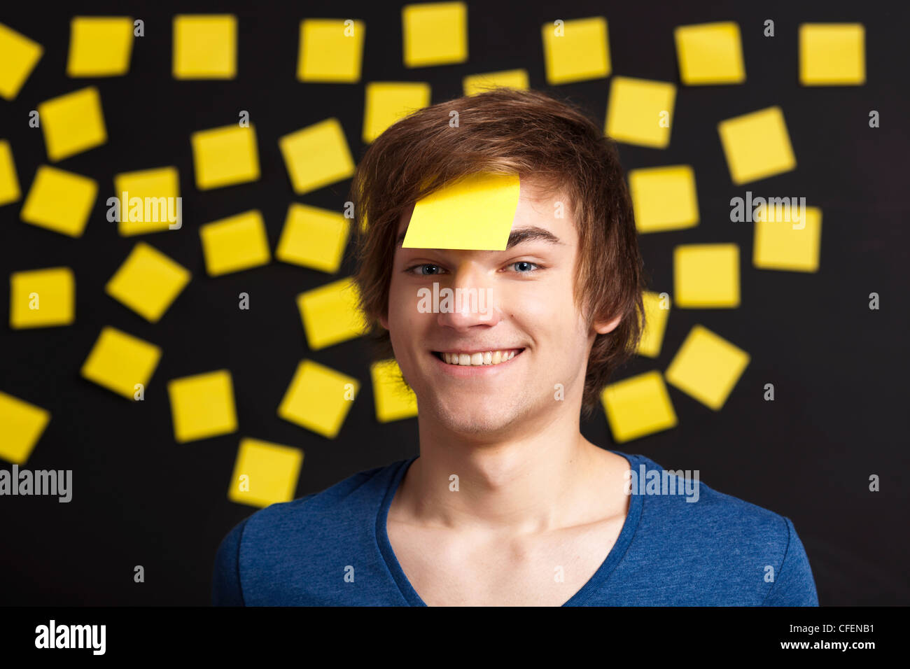Happy student with a reminder on the head, and with more yellow paper notes in the background - Stock Image