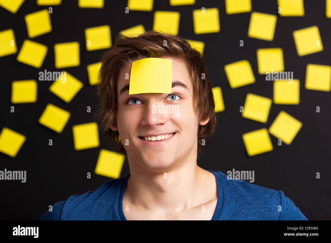 Happy student with a reminder on the head, and with more yellow paper notes in the background Stock Photo