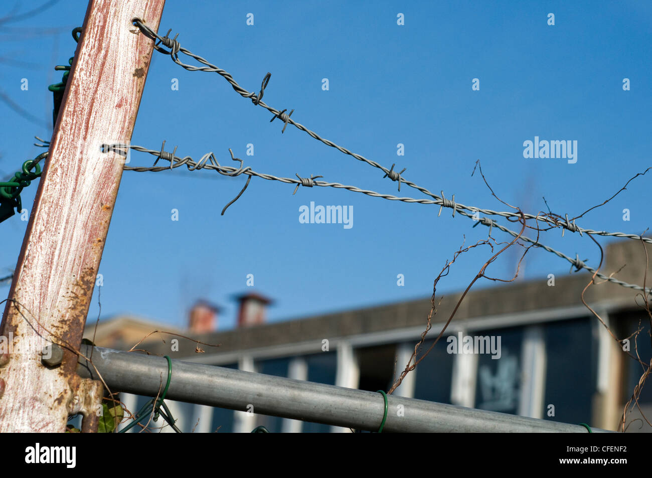 A section of barbed wire in front of a derelict building - Stock Image