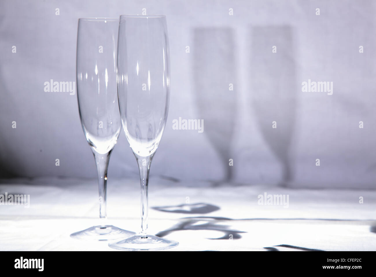 pair of crystal champagne flute glasses on white background with shadow - Stock Image