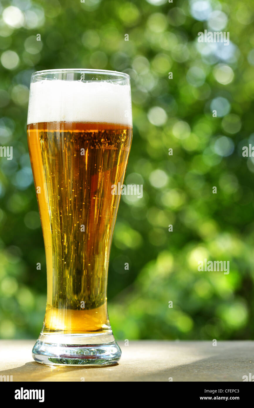 Beer glass at the table close-up, background is out of focus - Stock Image